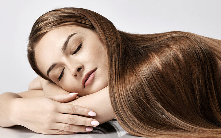 woman model with silky long straight hair lying and relaxing with eyes closed