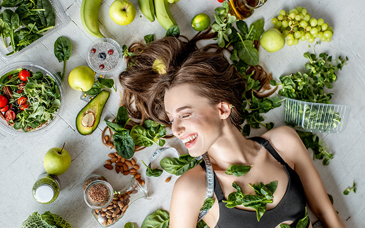 woman surrounded by various fruits