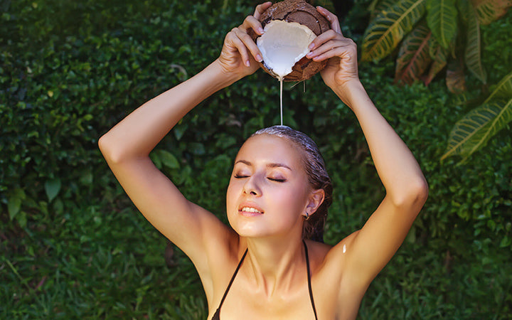 woman washing her hair with the pure coconut milk