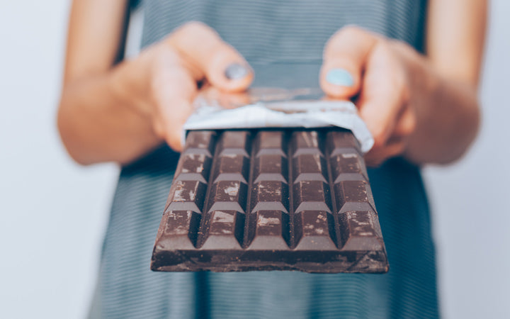 woman's hands holding unwrapped dark chocolate bar