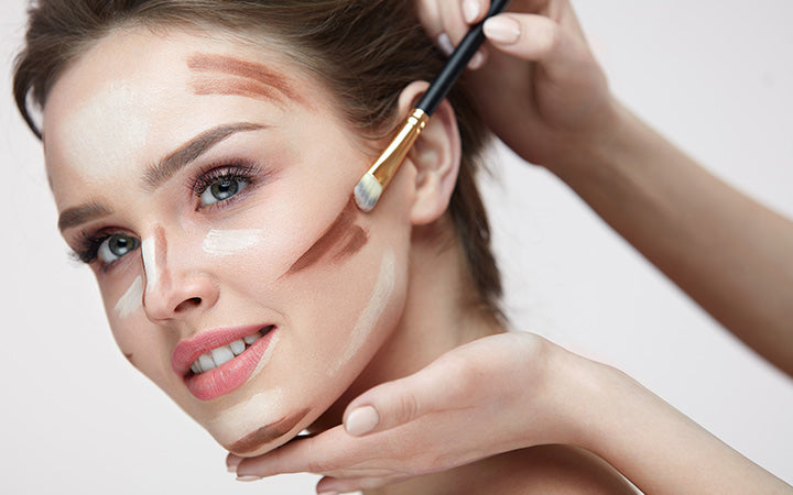 young female with smooth skin and fresh makeup and hands with brush applying make-up product