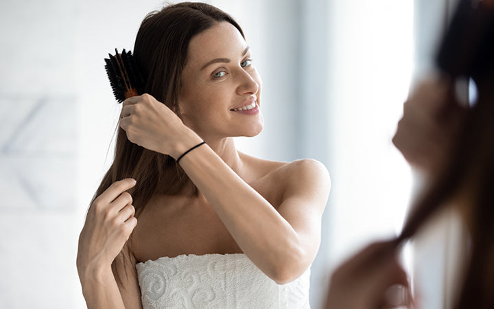 young lady model brushing long healthy hair look in mirror