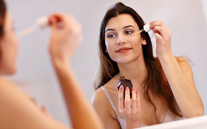 young woman applying serum in the bathroom