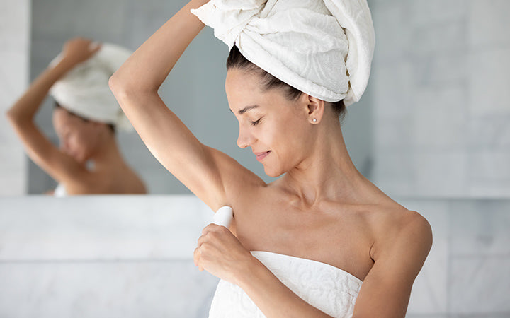 young woman with white bath towel on head applying antiperspirant