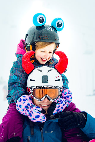A picture of a father and a daughter wearing fun helmet ears that attach to a helmet with velcro. the fither is wearing bison/devil horns and his daughter is wearing a blue frog eyes. Great helmet covers!