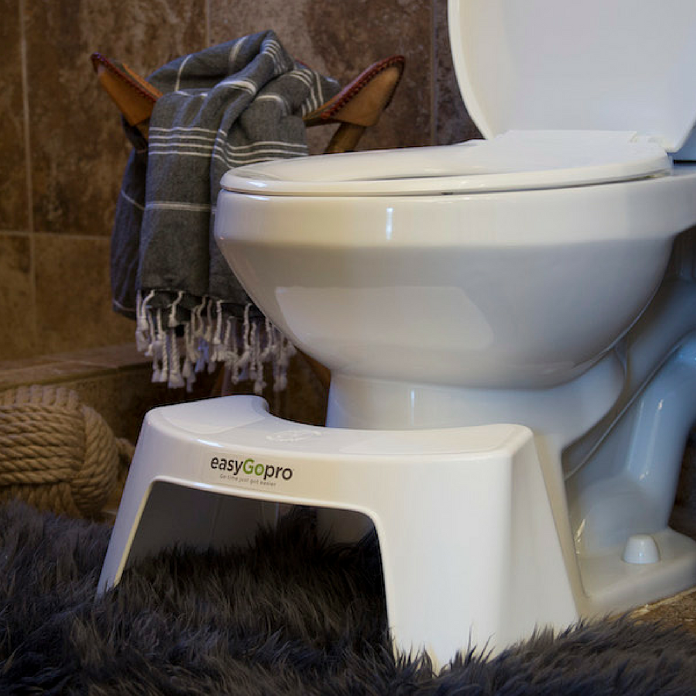 White easygorpo toilet stool in front of a toilet on top of a bronze fuzzy bathroom rug, in a manly bathroom.