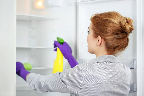 Woman cleaning her fridge