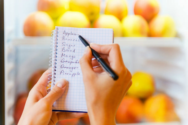 A notebook with a grocery list written in it.