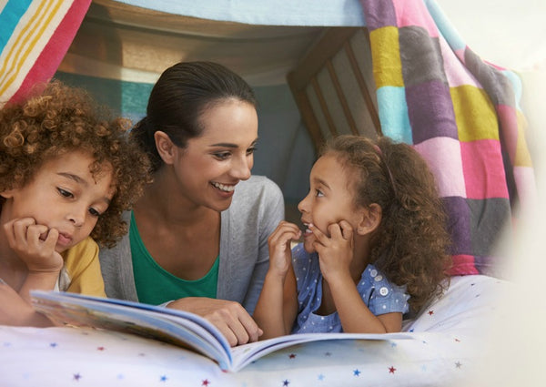 A mother reading a story to his children in a pillow fort