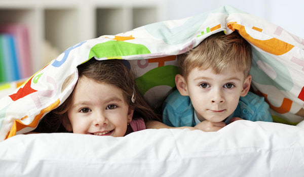 Kids in bed with blanket.