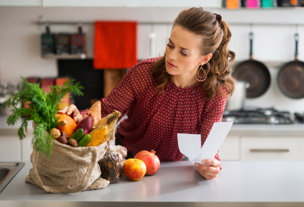 Woman looking at her groceries on her kitchen counter.