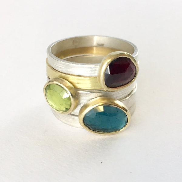 Garnet, peridot and London blue topaz stacking rings set in 18 ct gold bezel on silver bands by Wyckoff Smith Jewellery. Includes a textured 18 ct gold wedding ring.