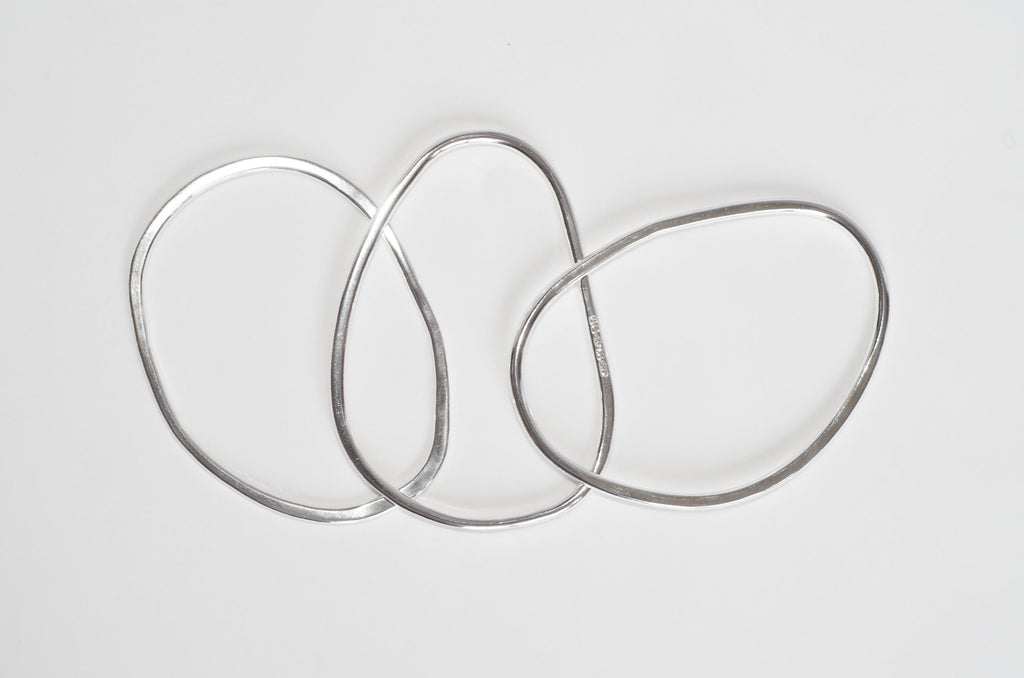 Assorted oval shaped silver bangles by Michele Wyckoff Smith