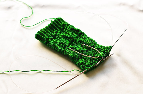 U shape silver cable needle on complicated green cable knit sock by Wyckoff Smith Jewellery www.wyckoffsmith.com