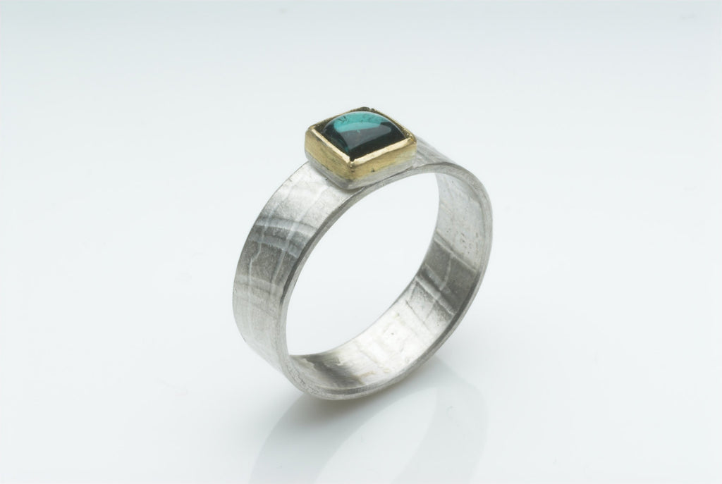 Square tourmaline in 18 ct gold with textured silver band.