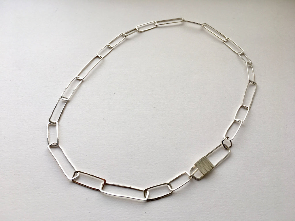 Silver paperclip chain with hammered texture.