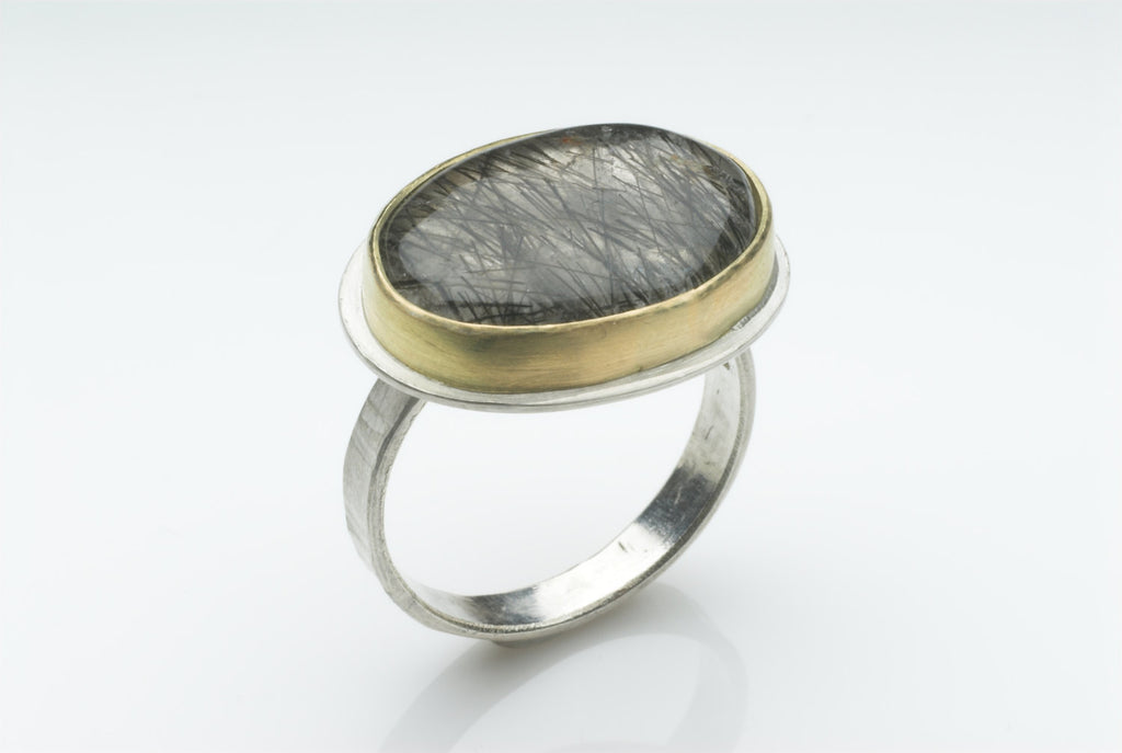 Rutilated quartz with gold bezel and textured silver band.