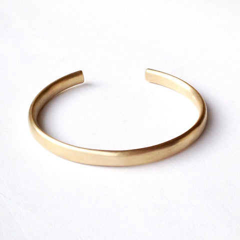 Oval gold open cuff bracelet.