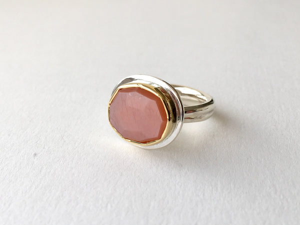 pink peach moonstone platform ring set in 18 ct gold on a silver ring.