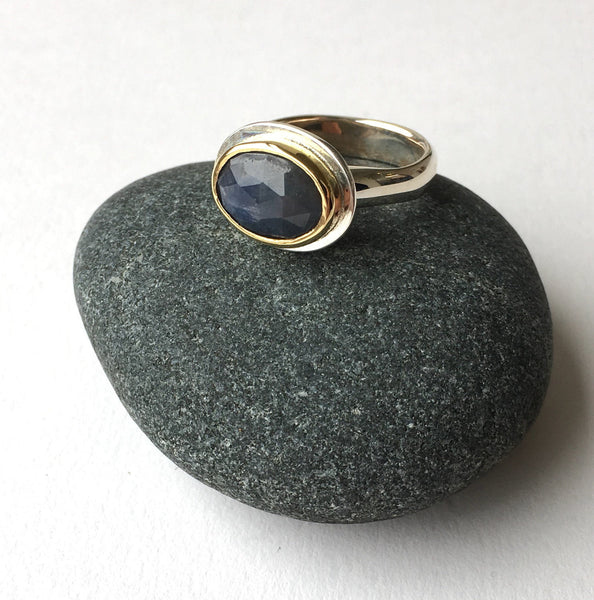 Denim blue faceted sapphire set in gold on silver ring.
