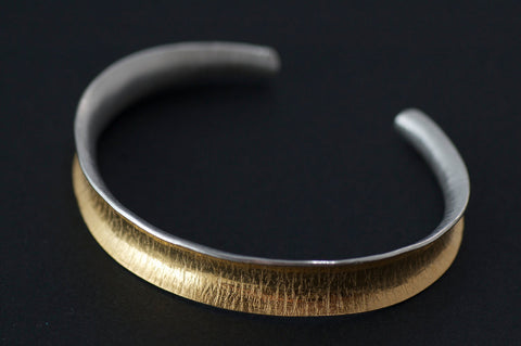 Gold and silver anticlastic curved open cuff bracelet with crepe texture.