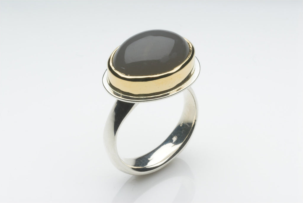 Grey moonstone platform ring set in 18 ct gold on a silver ring.