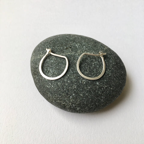 Hand forged silver hoop earrings with a U shape sitting on a pebble - Wyckoff Smith Jewellery