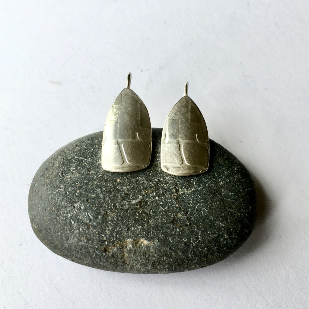 Silver spinnaker earrings with half grid texture on a pebble (option 1) on www.wyckoffsmith.com
