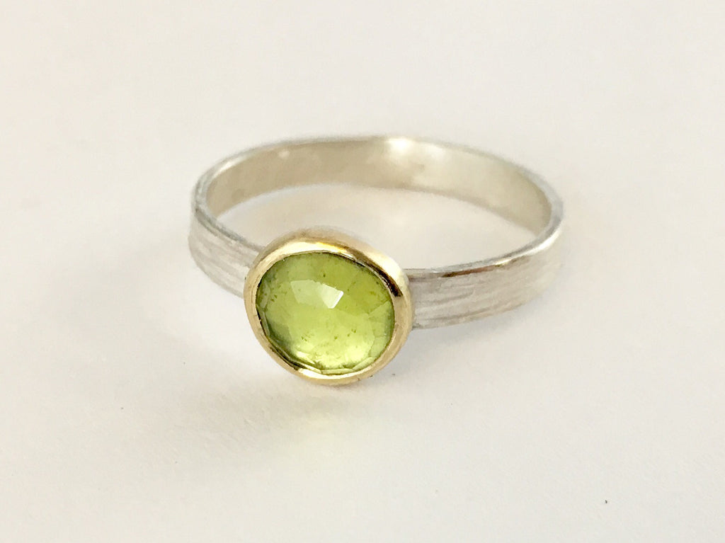 Light green faceted peridot ring set in 18 ct gold on a textured silver band by Michele Wyckoff Smith (UK)
