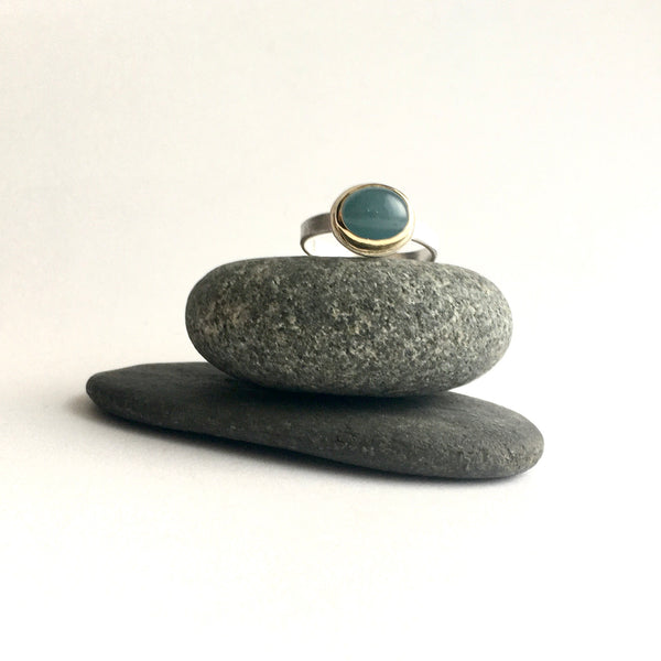 Front view of blue grey aquamarine cabochon set in 18 ct gold on top of two pebbles by Michele Wyckoff Smith on www.wyckoffsmith.com