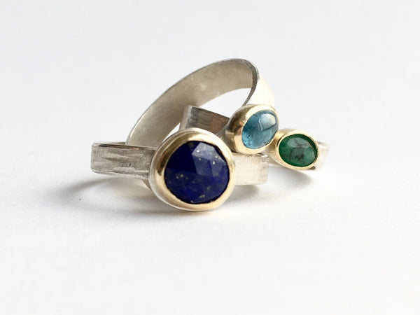 Jumble of silver and gold stacking rings by Michele Wyckoff Smith: gold flecked lapis lazuli, tourmaline and rough emerald