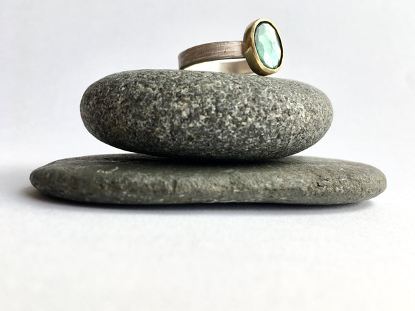 Blue tourmaline stacking ring sitting on top of two granite pebbles by www.wyckoffsmith.com