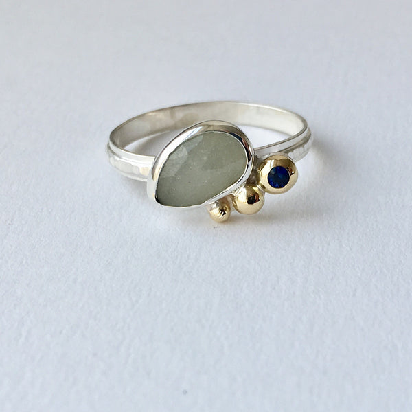 Larger grey faceted oval sapphire with 3 gold balls along side. There is a blue sapphire set in the largest 18 ct gold ball.