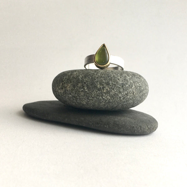 Front view of a green pear shaped indiocrase stacking ring on top of two pebbles. Silver and gold ring on www.wyckoffsmith.com