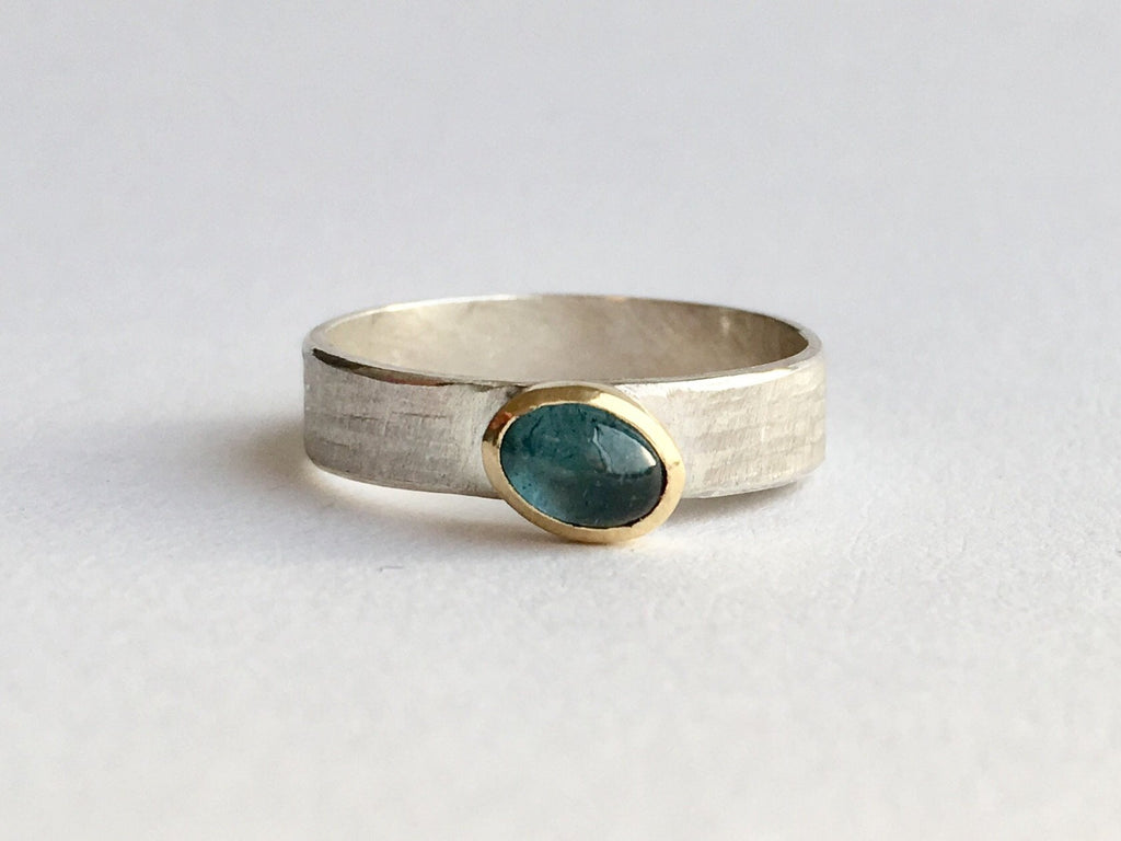 Oval tourmaline set in 18 ct gold on textured silver 4.75 mm wide band by Michele Wyckoff Smith