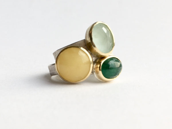 Stack of aquamarine, amber and emerald gemstone rings set in 18 ct gold on silver ring bands by Wyckoff Smith Jewellery