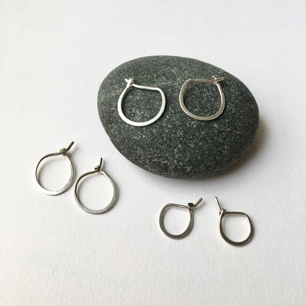 Assortment of hand forged silver hoop earrings sitting on a pebble - Wyckoff Smith Jewellery