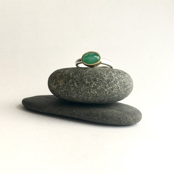 Front view of faceted chrysoprase set in 18 ct gold on a oval silver ring on top of two pebbles by Michele Wyckoff Smith on www.wyckoffsmith.com