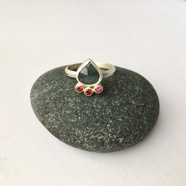 Blue green sapphire and rhodolite garnet ring on a pebble - Wyckoff Smith Jewellery
