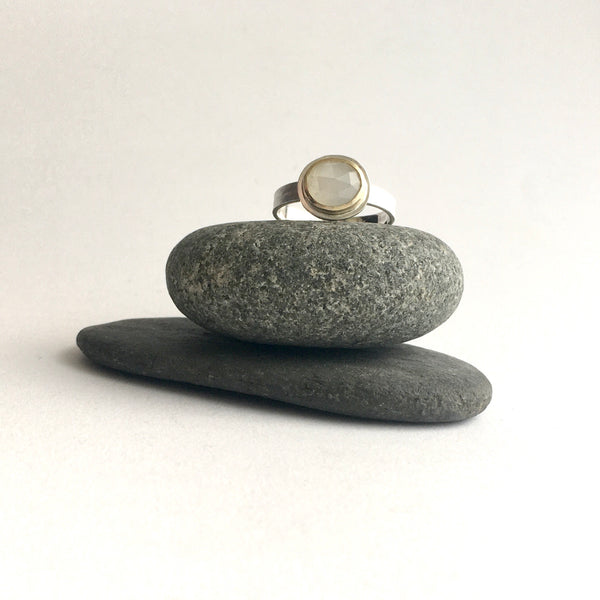 Front view of white moonstone set in 18 ct gold on silver textured band on top of two pebbles by Michele Wyckoff Smith on www.wyckoffsmtih.com stacking rings
