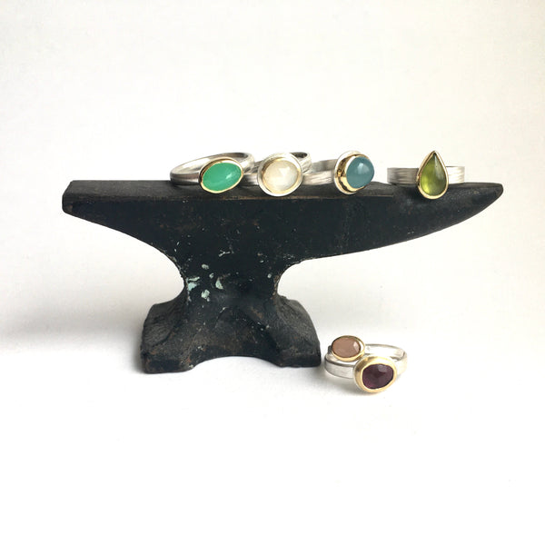 Side view of a collection of gemstone rings on a miniature jeweler's anvil on www.wyckoffsmith.com Left to right: chrysoprase, white moonstone, aquamarine, idiocrase (vesuvianite), peach moonstone and deep pink tourmaline