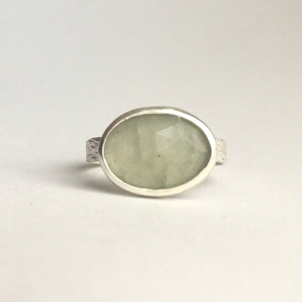Front view of grey green faceted prehnite gemstone ring set in silver with a textured ring available on www.wyckoffsmith.com