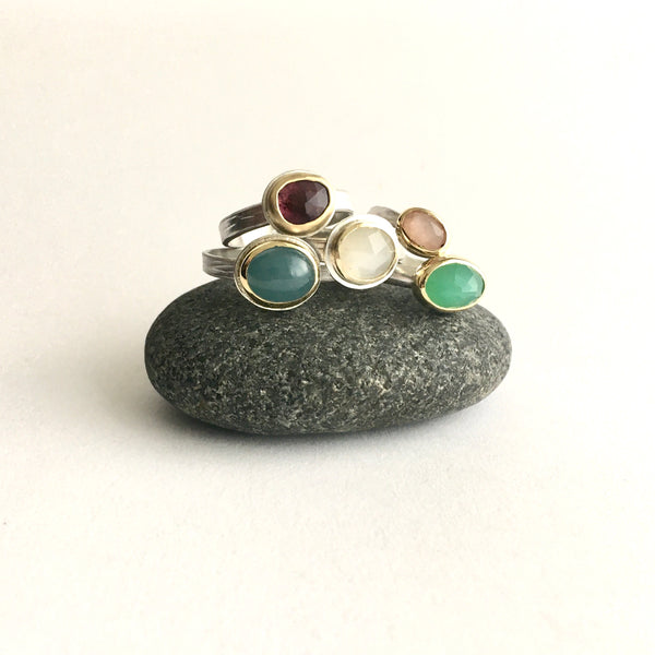 Collection of silver and gold gemstone stacking rings on top of a pebble by Michele Wyckoff Smith on www.wyckoffsmith.com left to right: aquamarine, deep pink tourmaline, white moonstone, peach moonstone and chrysoprase