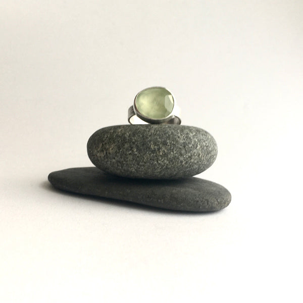 Faceted prehnite gemstone ring - front view on two pebbles available on www.wyckoffsmith.com