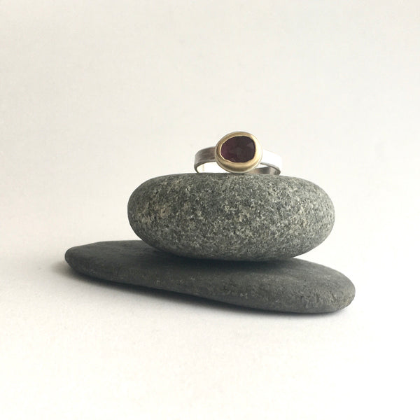 Front view of pink rose cut tourmaline set in 18 ct gold on a textured silver band on top of two pebbles on www.wyckoffsmith.com silver and gold jewelry