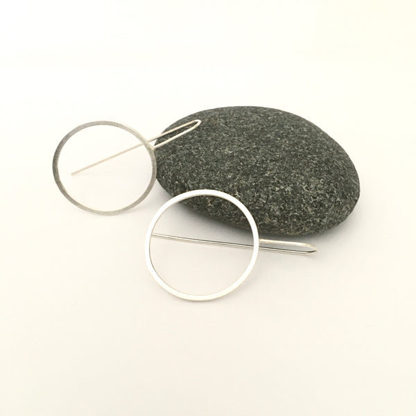 View of light silver circle earrings with grey pebble in background on www.wyckoffsmith.com