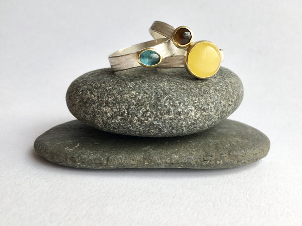 Silver and gold stacking rings on granite pebbles: blue tourmaline, smokey topaz and butter yellow amber by Michele Wyckoff Smith