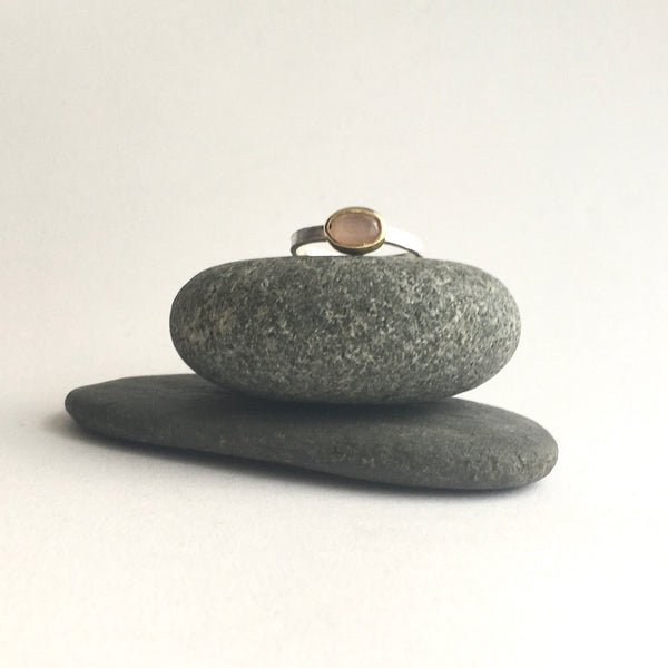 Peach moonstone set in gold on silver band on top of two pebbles by Michele Wyckoff Smith