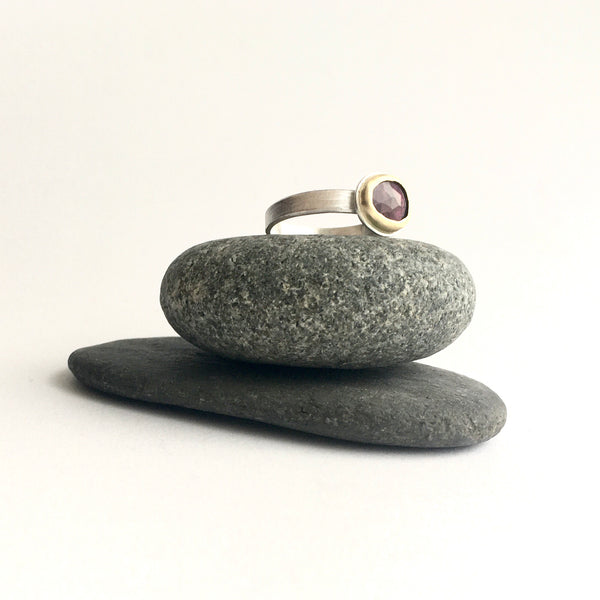 Side view of pink tourmaline ring on two pebbles on www.wyckoffsmith.com silver and gold jewellery