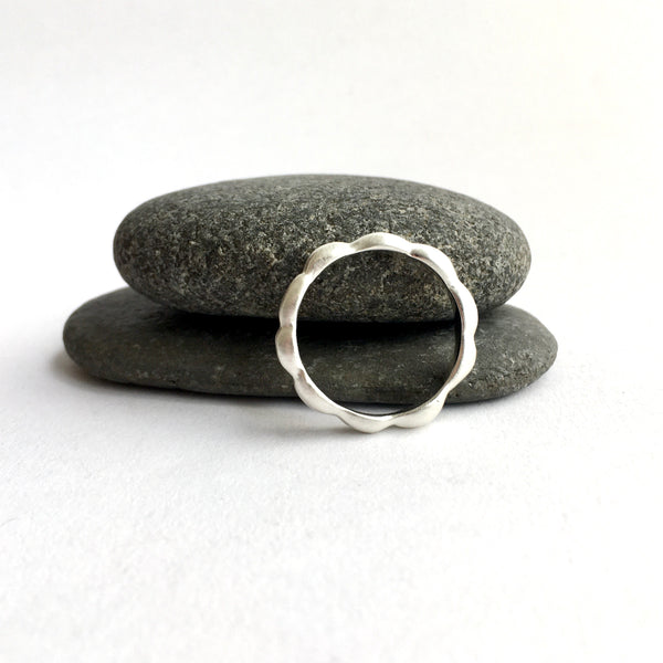 Side view of Kelp Ring next to two pebbles. Available on www.wyckoffsmith.com